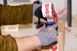 Mitarbeiter verschließt Karton mit ZOXS-Klebeband
