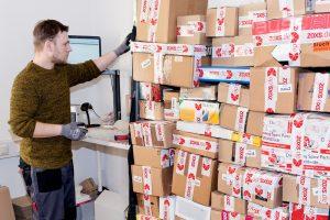 Mitarbeiter bereitet ZOXS Pakete für den Versand vor