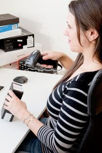 Mitarbeiterin scannt ein Produkt für den Verkauf auf buyZOXS
